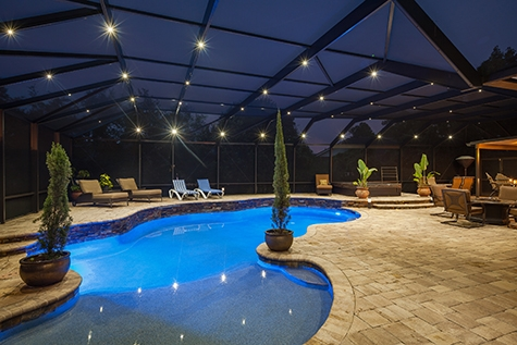 Pool with a large deck and screen enclosure with nebula light on the enclosure and in the pool