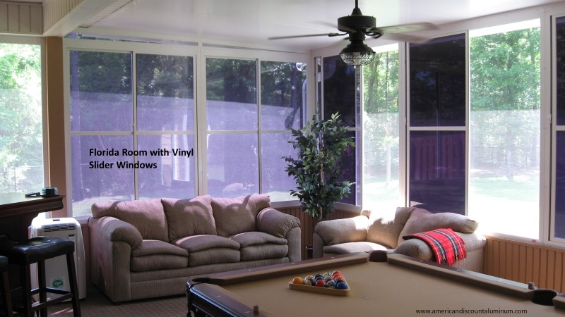 Sunroom with vinyl windows containing a couch and a pool table