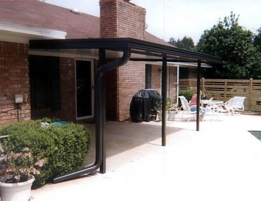 A bronze patio roof attached to a brick masonry home