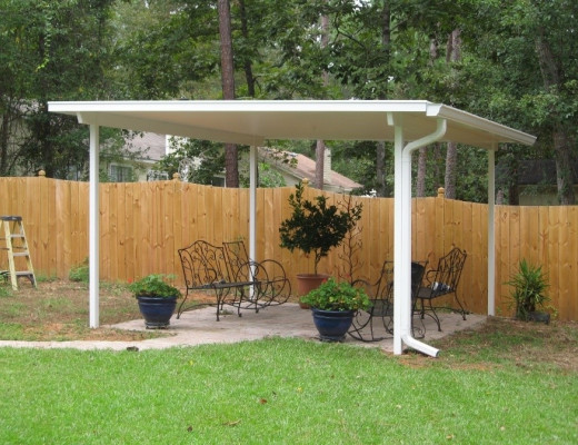 A free standing patio roof with plants and patio furniture