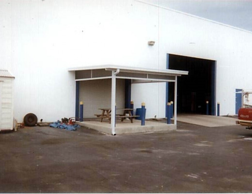 A white aluminum patio roof over a break area at a warehouse