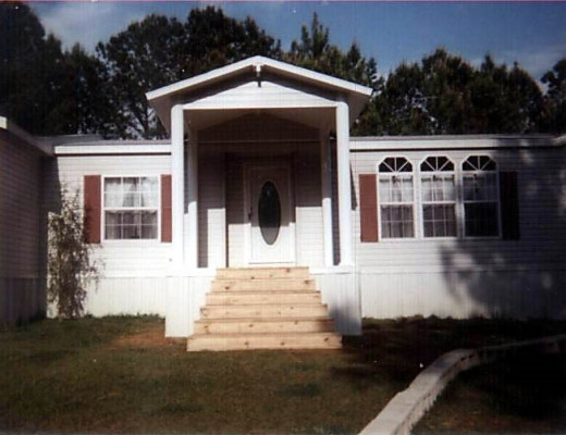 A white entryway with wood steps attached to a mobile home