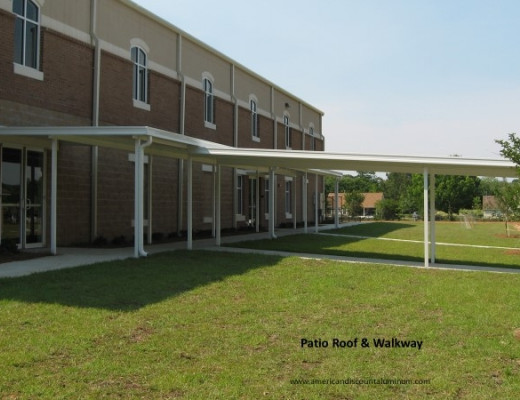A white aluminum patio roof and walkway attached to a commercial building