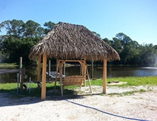 Tiki hut with wooden swing by waterway