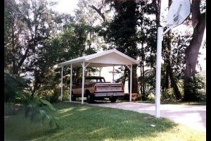 Carport with a truck parked underneath in a yard with a basketball court