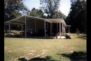 Gable hip carport attached to brick home