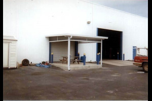 Patio roof on warehouse with wood picnic table