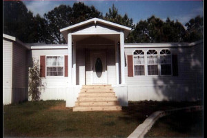 Covered entryway with wood steps attached to mobile home