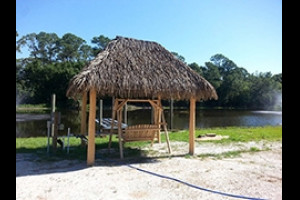 Tiki hut with a swing on the banks of a pond
