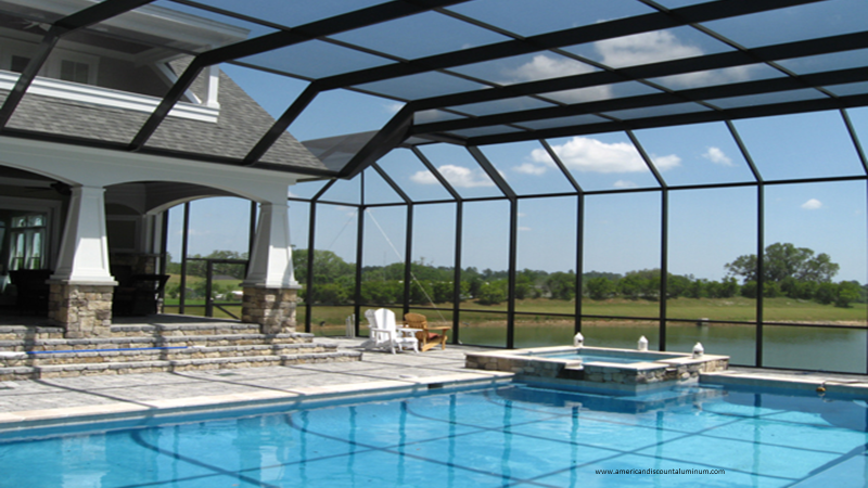 Screened in pool with large black enclosure overlooking a lake